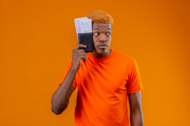 Chico guapo joven con camiseta naranja con billete de avión mirando a un lado preocupado de pie sobre la pared naranja Foto gratis
