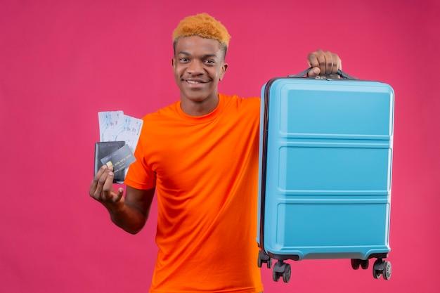 Chico guapo joven con camiseta naranja con maleta de viaje y billetes de avión sonriendo confiado positivo y feliz de pie sobre la pared rosa Foto gratis