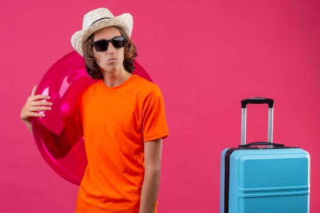 Chico guapo joven en camiseta naranja y sombrero de verano con gafas de sol negras sosteniendo un anillo inflable mirando a un lado con el ceño fruncido de pie con maleta de viaje sobre fondo rosa Foto gratis