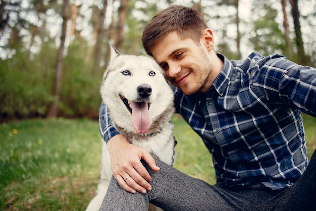 Chico guapo en un parque de verano con un perro Foto gratis