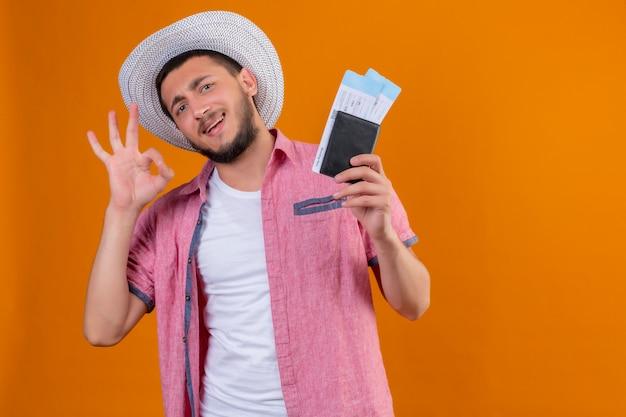 Chico guapo viajero joven con sombrero de verano con billetes de avión mirando a la cámara salió y feliz sonriendo alegremente haciendo bien firmar listo para viajar de pie sobre fondo naranja Foto gratis