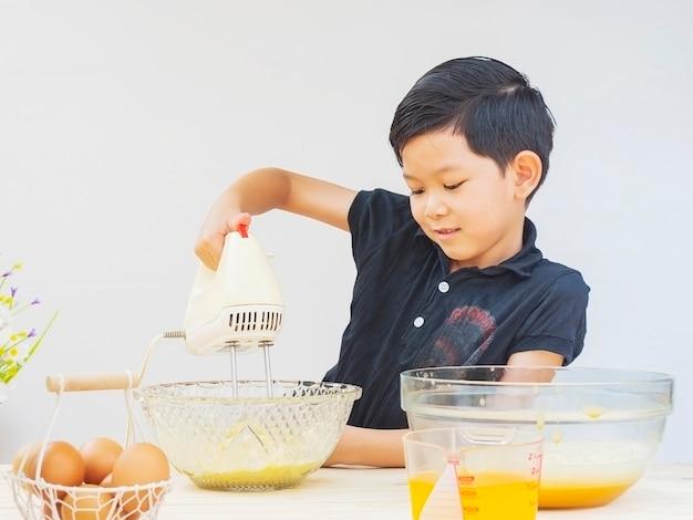 Un chico esta haciendo pastel Foto gratis