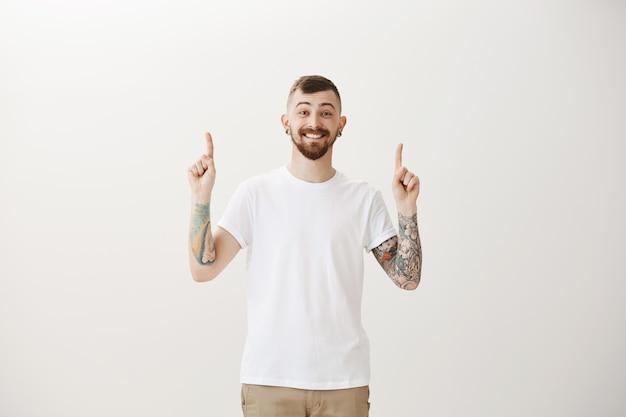 Chico hipster emocionado apuntando con el dedo hacia arriba y sonriendo feliz Foto gratis