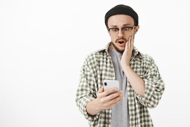 Chico impopular que se sorprende al recibir me gusta en la última publicación en la red social jadeando con la boca abierta sosteniendo la mano en la mejilla mirando sorprendido y asombrado por la pantalla del teléfono inteligente sobre una pared blanca Foto gratis