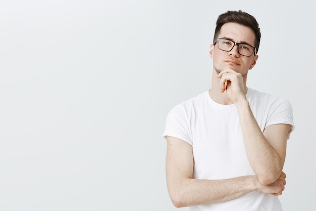 Chico inteligente reflexivo en gafas pensando, mirando intrigado Foto gratis