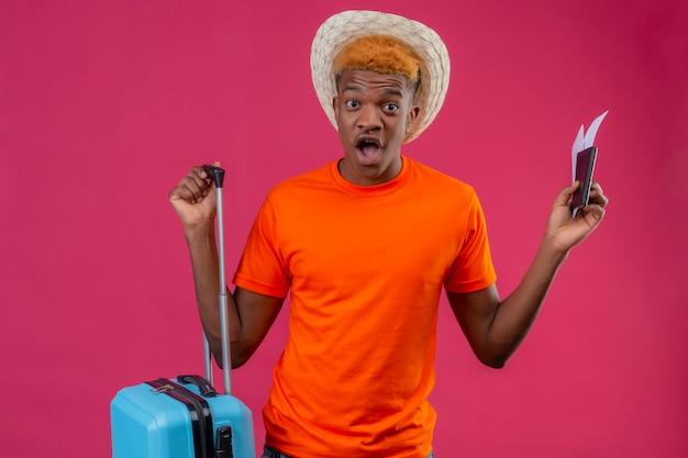 Chico joven guapo viajero con sombrero de verano con camiseta naranja con maleta de viaje y billetes de avión Foto gratis
