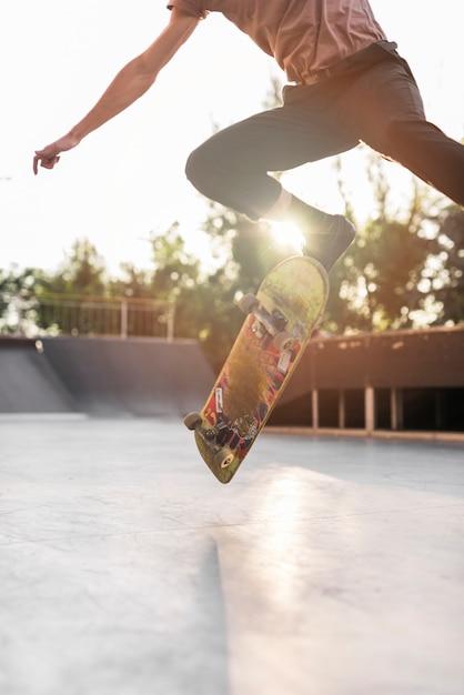 Chico joven patinando con patineta en la calle Foto gratis