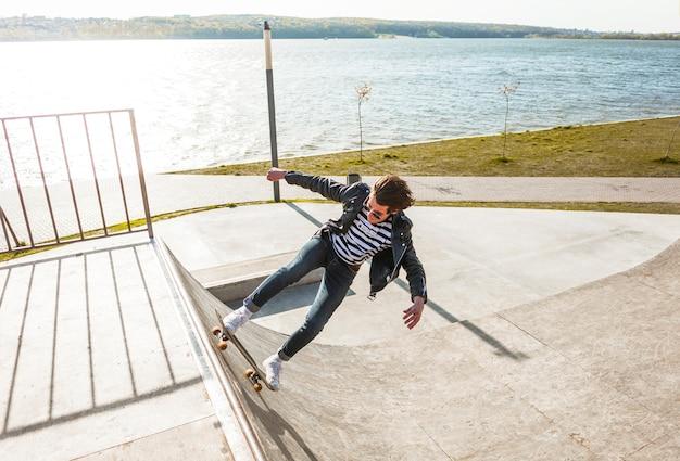 Chico joven con su monopatin en la pista de skate Foto gratis