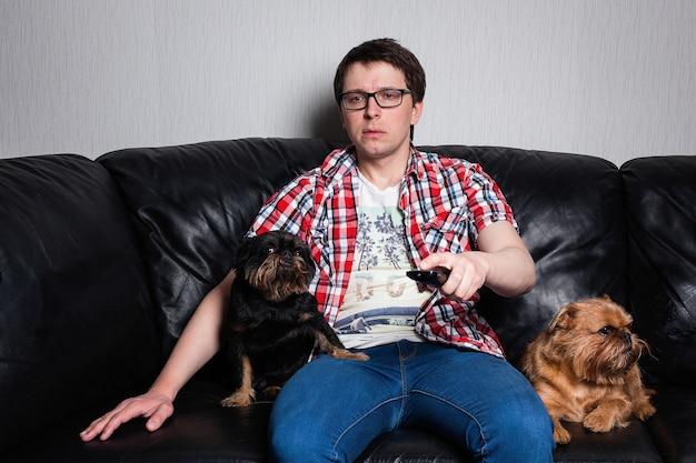 Un chico joven viendo la tele en casa con perros. Foto Premium
