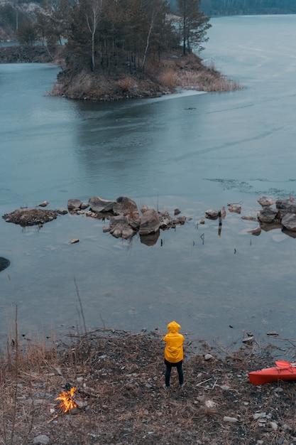 Chico en el lago hace un fuego Foto gratis