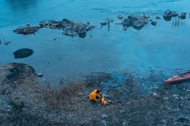 El chico del lago hace fuego Foto gratis