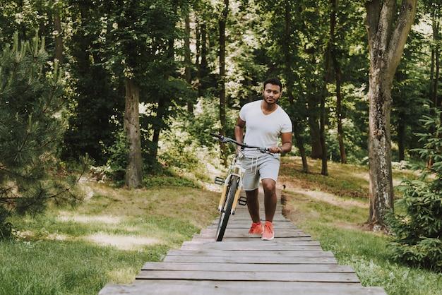 Chico latino en el parque caminando con bicicleta Foto Premium