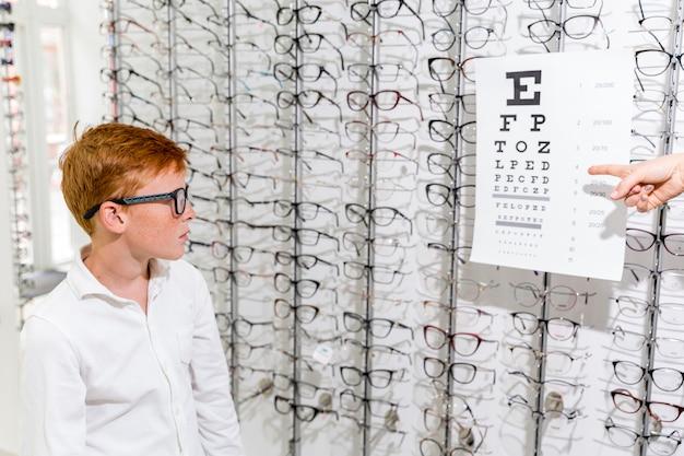Chico lindo mirando la tabla de snellen en clínica de óptica Foto gratis