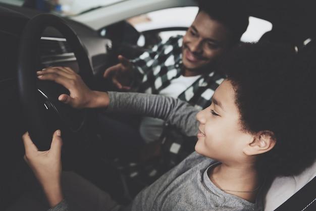 Chico lindo en el volante papá enseña a conducir. Foto Premium