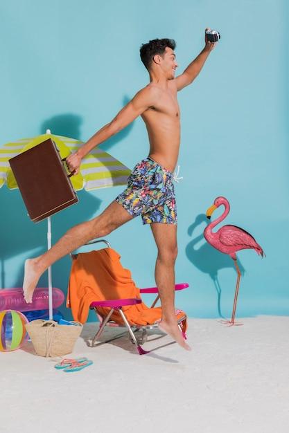 Chico con maleta corriendo en la playa Foto gratis