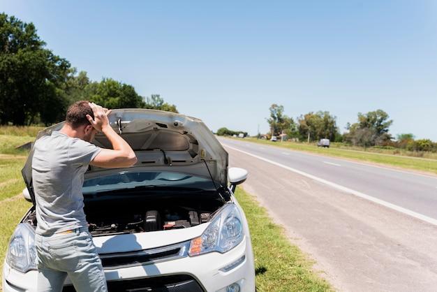 Chico mirando coche averiado Foto gratis