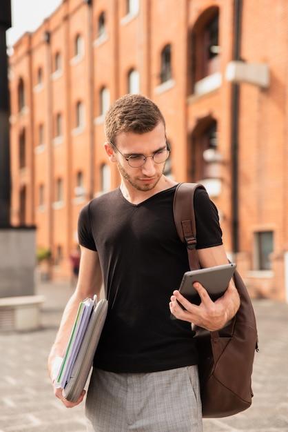 Chico mirando su tableta y sosteniendo sus notas Foto gratis