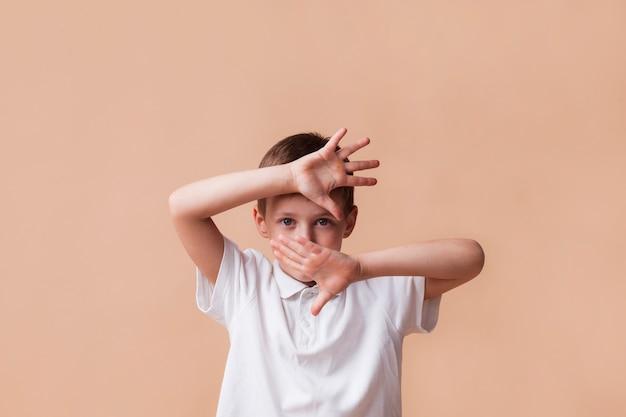 Chico mostrando parada gesto mirando a la cámara sobre fondo beige Foto gratis