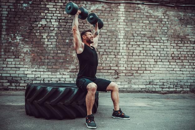 Chico musculoso haciendo ejercicios con pesas contra una pared de ladrillos Foto Premium