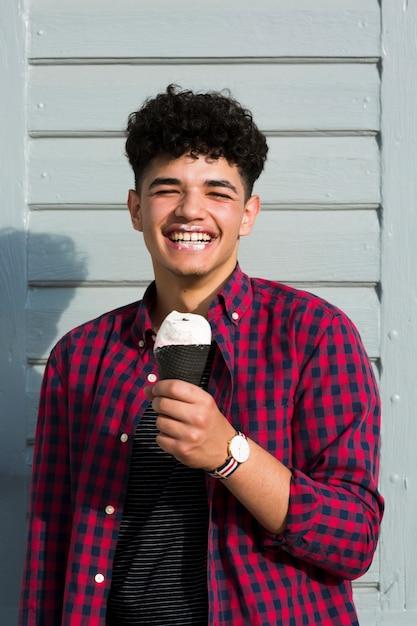Chico negro riendo en camisa a cuadros con helado Foto gratis