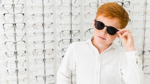 Chico pecosa con anteojos negros posando en tienda de óptica Foto gratis
