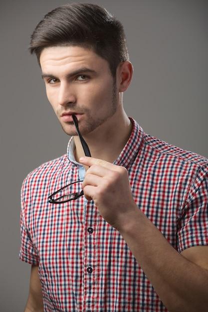 Chico pensativo con un grillete de gafas en la boca Foto Premium