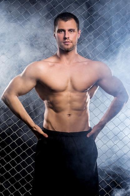 Chico poderoso con una cadena mostrando sus músculos Foto gratis