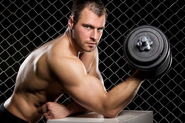 Chico poderoso con pesas que muestra los músculos en la valla Foto gratis