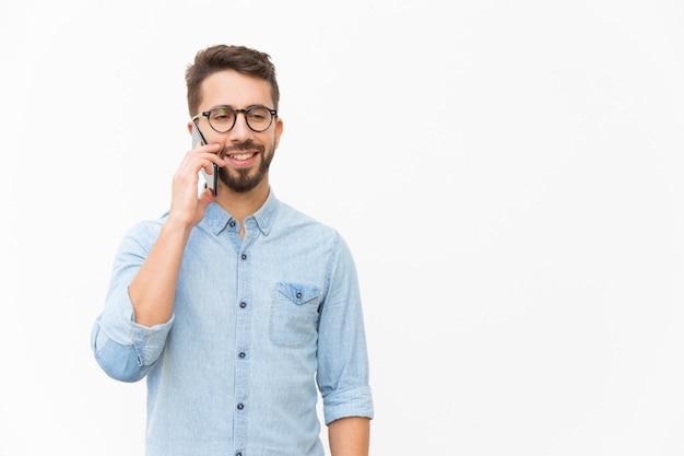 Chico positivo hablando por celular Foto gratis