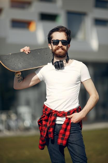 Chico con skate en la calle Foto gratis