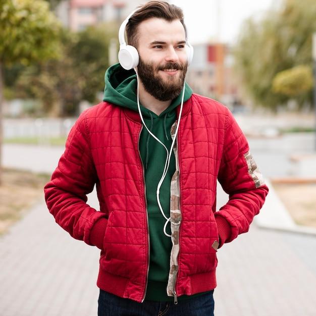 Chico sonriente de tiro medio con barba y auriculares Foto gratis