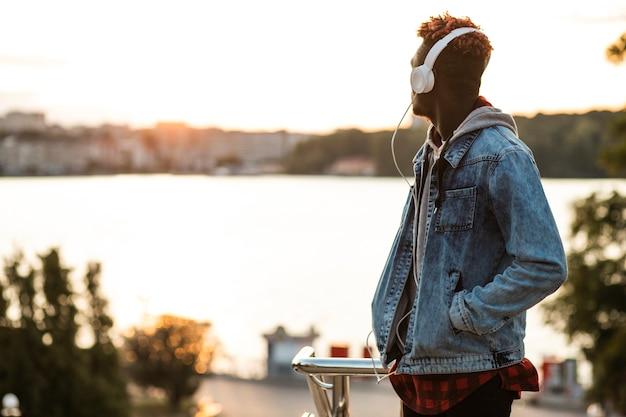 Chico de tiro medio con auriculares y chaqueta de jeans Foto gratis