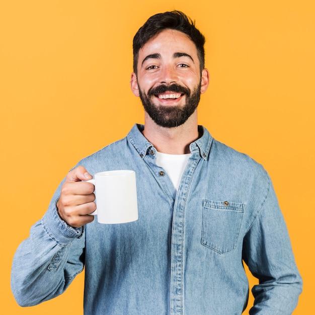 Chico de tiro medio sonriente sosteniendo una taza Foto gratis