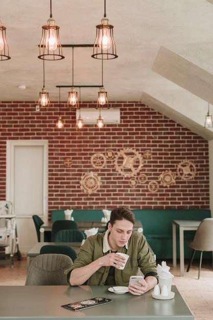 Chico tomando café en un restaurante Foto gratis