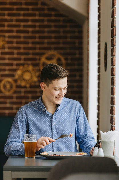 Chico tomando una cerveza en un restaurante Foto gratis