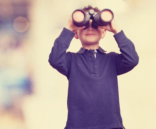 Chico usando prismáticos Foto gratis