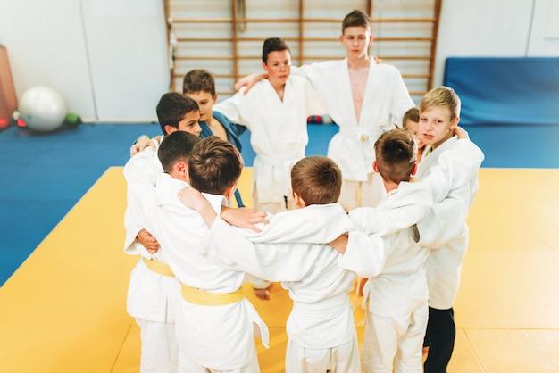 Chicos en kimono en el entrenamiento de judo para niños en interiores. jóvenes luchadores en gimnasio, arte marcial para la defensa Foto Premium