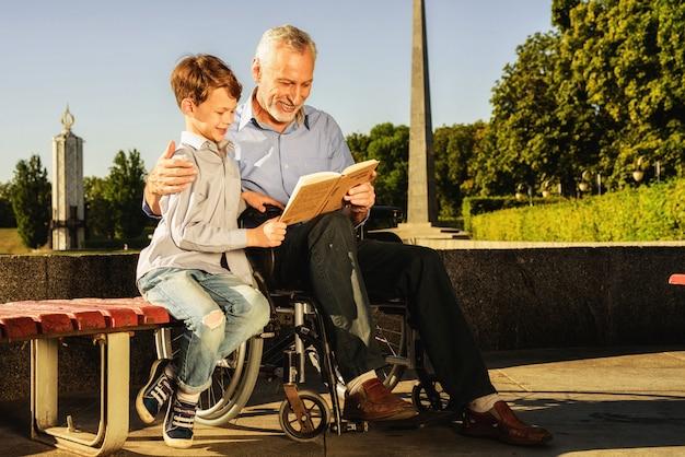 Chicos leen el libro juntos. rehabilitación al aire libre. Foto Premium