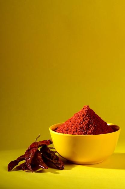 Chile en polvo en un tazón amarillo. pimiento rojo frío Foto Premium