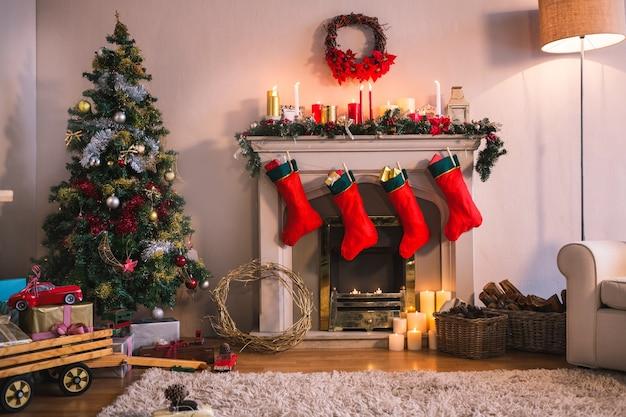 chimenea con calcetines rojos colgando y un rbol de navidad