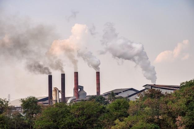 Chimenea industrial con emisión de polución de humo al cielo. Foto Premium