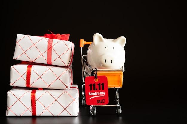China, 11.11 venta de un solo día, etiqueta de boleto roja colgada en un mini carrito de la compra con hucha Foto Premium