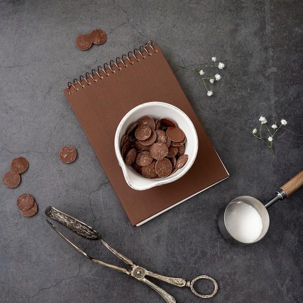 Chips de chocolate en un cuaderno marrón sobre un fondo gris Foto gratis