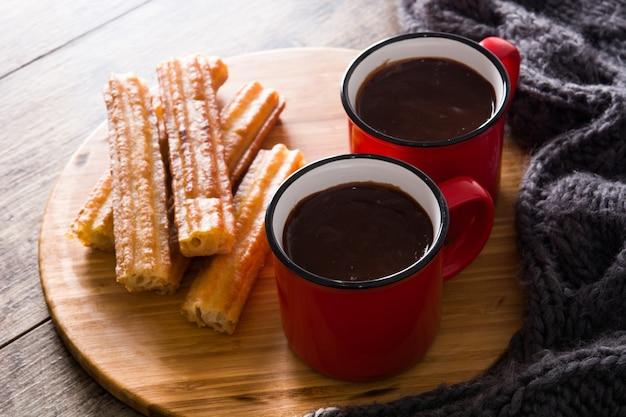 Chocolate caliente con churros en mesa de madera. Foto Premium