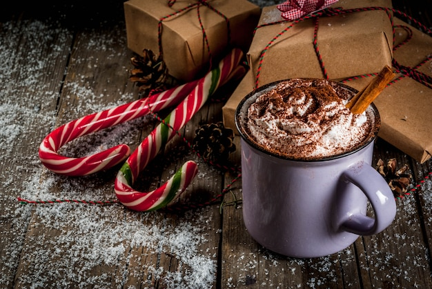 Chocolate caliente con crema batida y especias, regalos de navidad y bastones de caramelo. Foto Premium