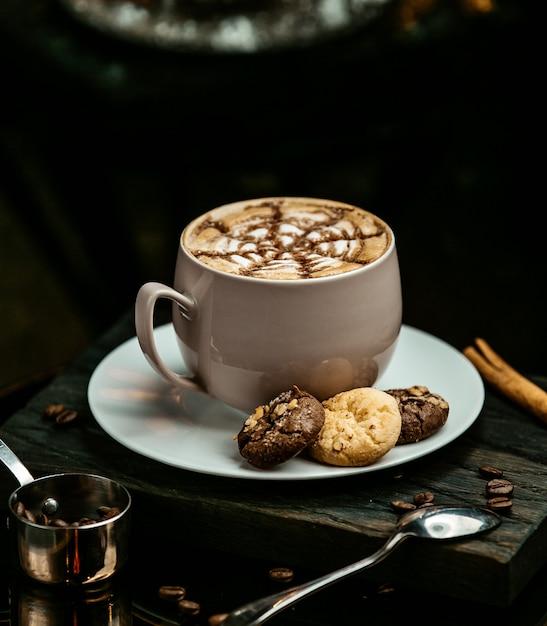 Chocolate caliente servido con galletas Foto gratis
