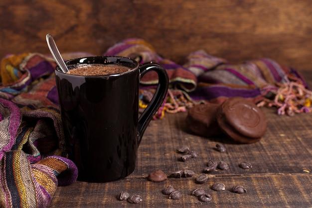 Chocolate caliente en taza con galletas y chips de cacao. Foto gratis