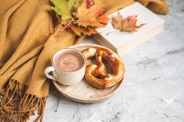 Chocolate caliente tiempo otoño panadería manta pretzel hojas amarillas sobre fondo Foto Premium