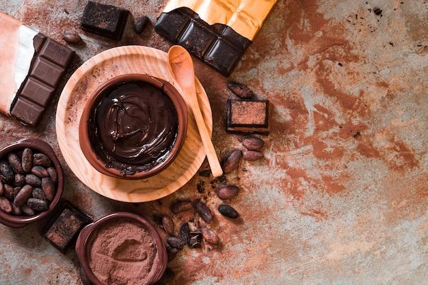 Chocolate derretido y barra de chocolate hecha con granos de cacao en la mesa Foto Premium