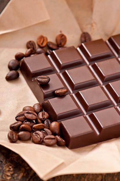 Chocolate y granos de café sobre papel beige. Foto gratis